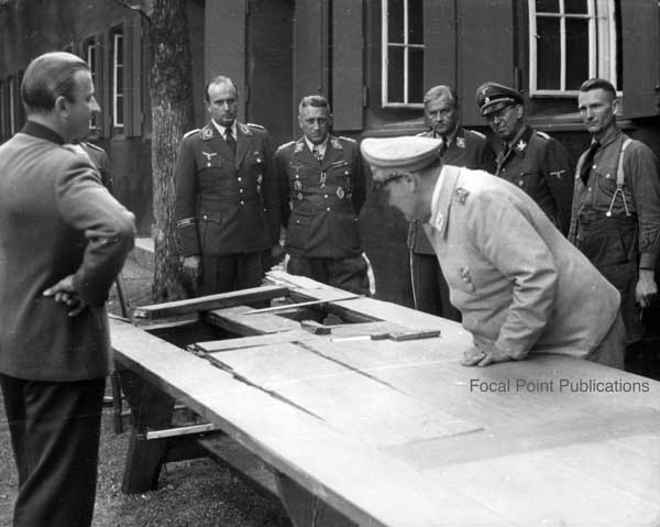 Hermann Göring inspects the table damaged by the traitors' bomb